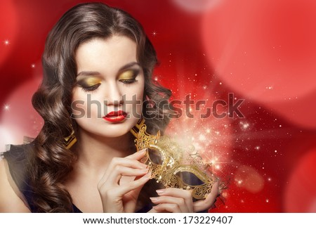 Young beautiful woman holding golden carnival mask. - stock photo