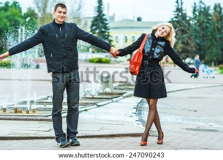 Young beautiful woman holding hand of her boyfriend in city autumn park. - stock photo