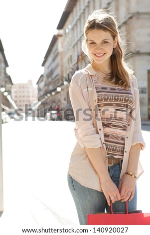 Young beautiful woman holding paper bags while visiting a city center during a sunny day, smiling at the camera with her shopping. - stock photo