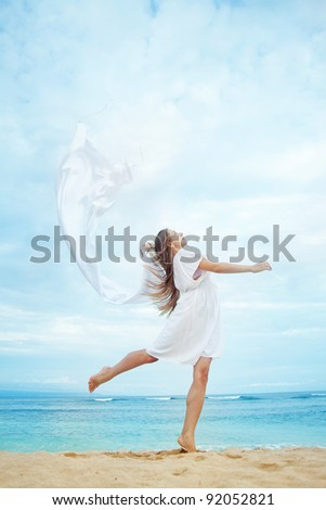 Young beautiful woman holding white flag near ocean, Indonesia, Bali - stock photo