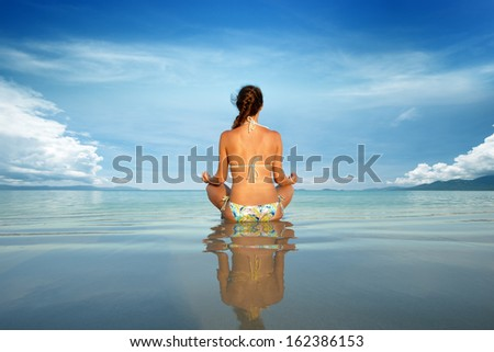 Young beautiful woman in a lotus position on a background of blue sky and island. - stock photo