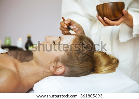 Young beautiful woman in a mask for the face of the therapeutic white mud. Spa treatment - stock photo