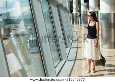 Young beautiful woman in airport while waiting for flight - stock photo