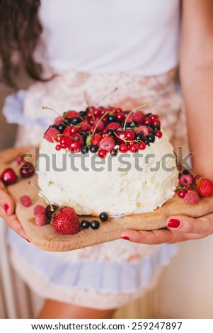 Young beautiful woman in an apron making cake with cream and berries at the kitchen - stock photo