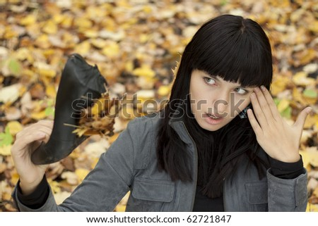 Young beautiful woman in autumn park with shoes. - stock photo