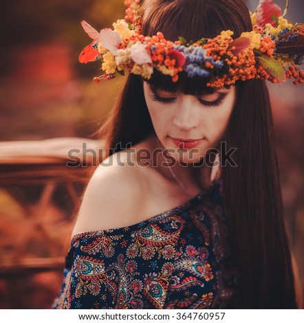 Young beautiful woman in autumn wreath on head - stock photo