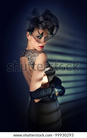 young beautiful woman in black dress and gloves - stock photo