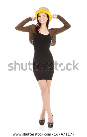 Young beautiful woman in black dress and golden hat. Isolated on white. - stock photo