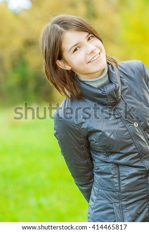 Young beautiful woman in black jacket against ridge fence. - stock photo