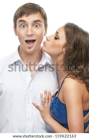 Young beautiful woman in blue dress kisses cheek surprised man, isolated on white background. - stock photo
