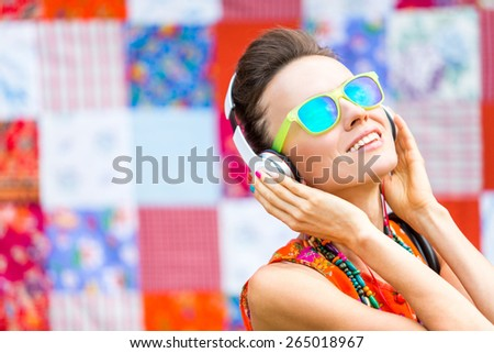 Young beautiful woman in bright outfit enjoying the music over bright background. soft image - stock photo