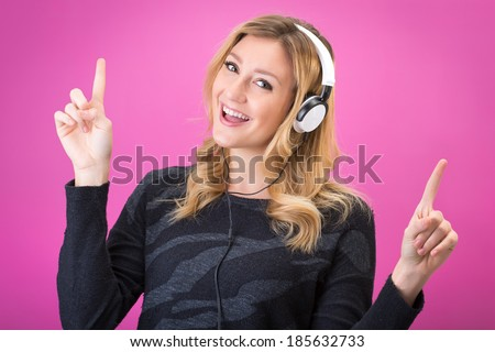 Young beautiful woman in bright outfit enjoying the music with her headphones. Studio portrait on pink background - stock photo