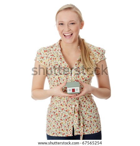 Young beautiful woman in casual clothes with house model - real estate - stock photo