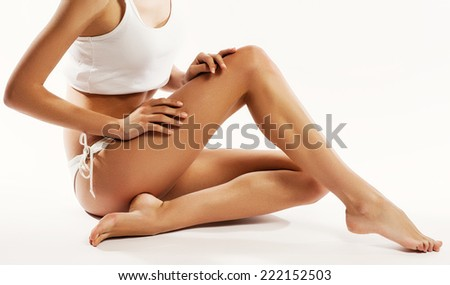 Young beautiful woman in cotton underwear sitting on white background - stock photo