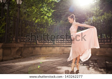 Young beautiful woman in elegant pink dress and ballet shoes in the garden. - stock photo