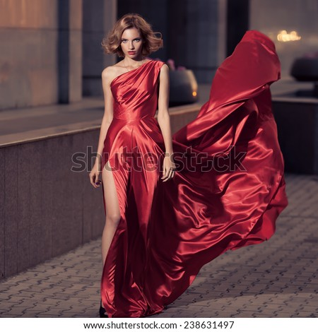 Young Beautiful Woman In Fluttering Red Dress. City Background. - stock photo