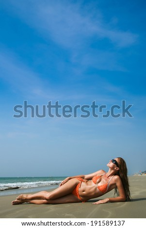 Young beautiful woman in orange swimwear lying on the beach - stock photo