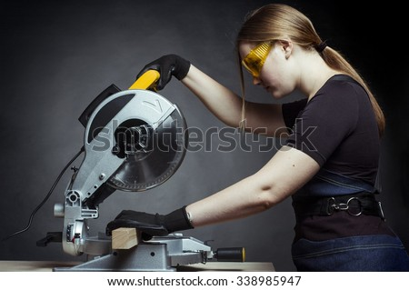 young beautiful woman in overalls and glasses with disk saw preparing for cutting. Photo on black background. - stock photo