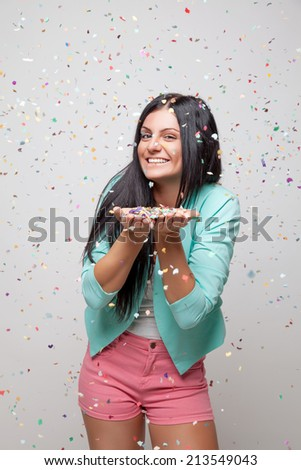 Young beautiful woman in party mood with confetti all around - stock photo