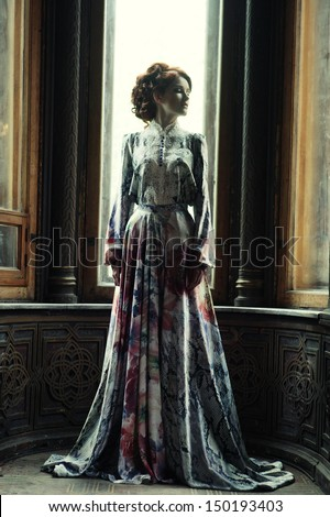 young beautiful woman in pink dress posing in luxury palace - stock photo