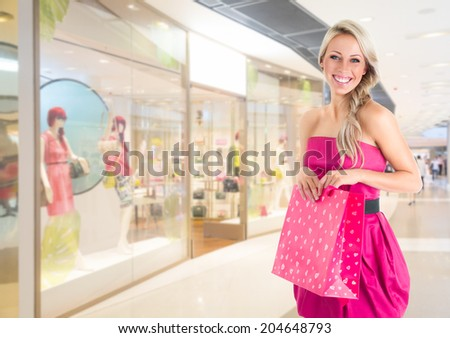 Young beautiful woman in pink mini dress at shopping mall - stock photo