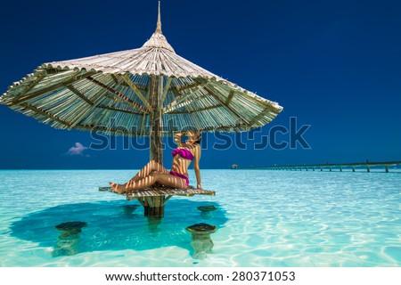 Young beautiful woman in purple bikinis under beach umbrella in the ocean - stock photo