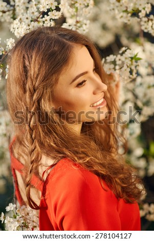 Young beautiful woman in red dress enjoying smell of blooming tree on a sunny day - stock photo