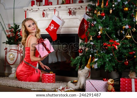Young beautiful woman in red dress with gift sits near Christmas tree at home. New year and Christmas. - stock photo