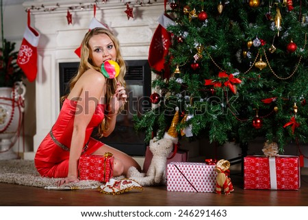 Young beautiful woman in red dress with lollipop sits near Christmas tree at home. New year and Christmas. - stock photo