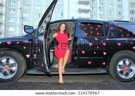 Young beautiful woman in red out of black wet offroader with stickers hearts. Pink wedding. - stock photo