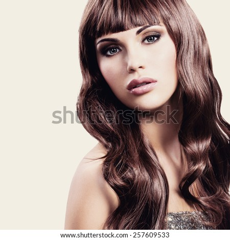 Young beautiful woman in silver dress posing at studio over white background. - stock photo
