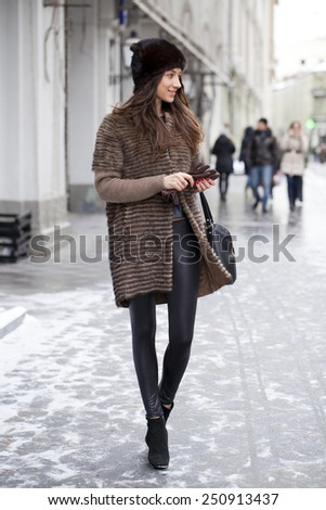 Young beautiful woman in stylish mink coat on a background of a winter street - stock photo