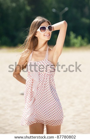 Young beautiful woman in summer dress and sunglasses on the beach - stock photo