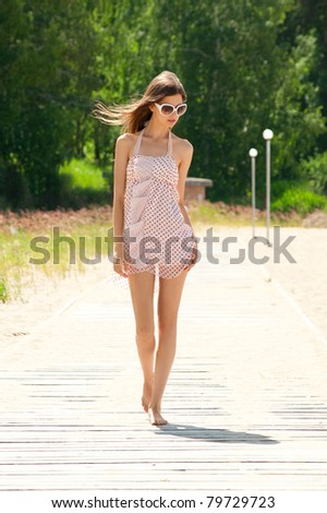 Young beautiful woman in summer dress and sunglasses outdoors - stock photo