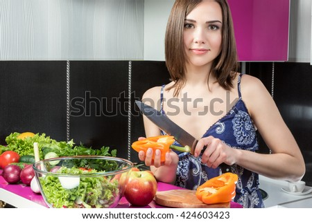 Young beautiful woman in the kitchen cleans pepper using large kitchen knife - stock photo