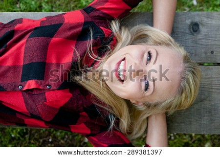 young beautiful woman in the nature on a bench smiling relaxed maybe in a park - stock photo
