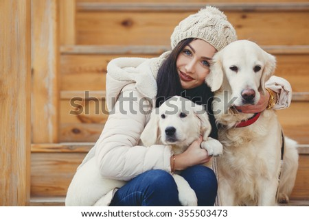 young beautiful woman in warm clothes with white labrador retrievers. dogs and woman. outdoor portrait. Pets and girl. Beautiful woman playing with her dogs, Puppy - stock photo