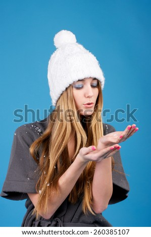 Young beautiful woman in white winter hat over blue background - stock photo
