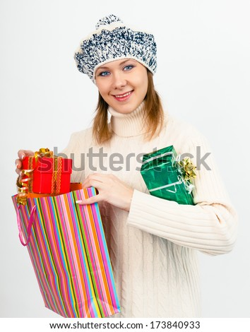 young beautiful woman in winter hat with gifts - stock photo