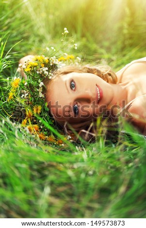 young beautiful woman in wreath of flowers lies in the green grass outdoors in nature - stock photo
