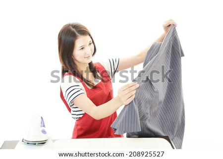 Young beautiful woman ironing clothes - stock photo