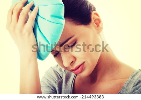 Young beautiful woman is haveng a headache and holding ice bag. Isolated on white. - stock photo