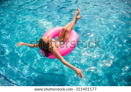Young beautiful woman is relaxing in swimming pool with rubber ring. - stock photo