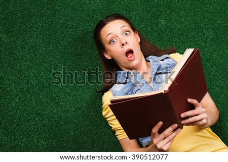 Young beautiful woman is surprised about something she had read in a book.Surprised woman with a book - stock photo