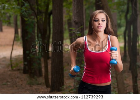 Young beautiful woman jogging in summer park - stock photo