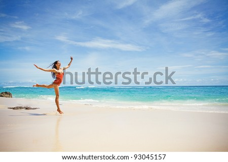 Young beautiful woman jumping over the sand near ocean, Bali, Indonesia - stock photo