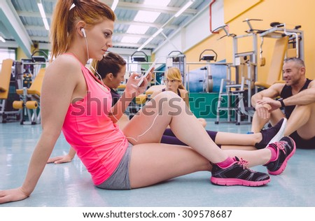 Young beautiful woman listening music in her smartphone while a friends talking sitting on the floor of fitness center - stock photo