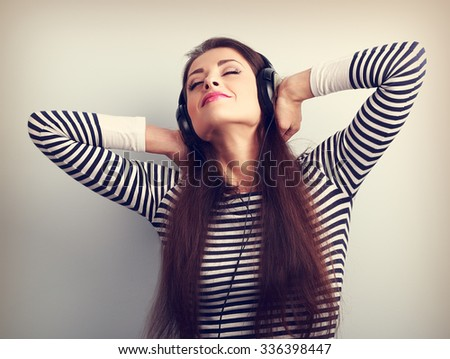 Young beautiful woman listening the music from headphones with closed enjoying eyes. Vintage toned portrait - stock photo