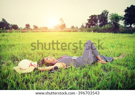 Young beautiful woman listening to music while lying down on green grass - stock photo