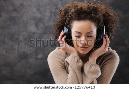Young beautiful woman listening to music with headphones - stock photo